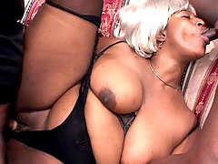 Curvy black babe Ebony Charm sucks on one cock while letting the other pound her wet pussy